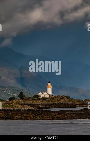 Un faro en un islote de mareas en un día tempestuoso Imagen De Stock