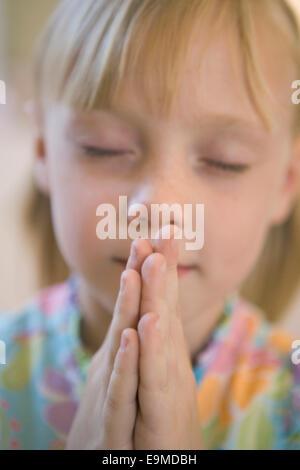 Niña rezando con los ojos cerrados Imagen De Stock
