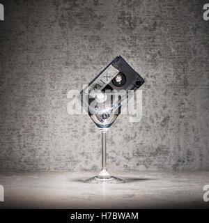 Mezcla de música para una fiesta. Cinta mezclados en un cóctel de vidrio. Bodegón con símbolo Imagen De Stock