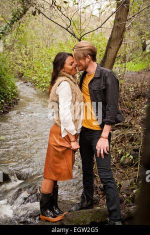 Mujer y hombre acerca a kiss junto a un arroyo. Imagen De Stock