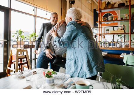 Abrazos y Madre Hija de felicitación en cafe Imagen De Stock