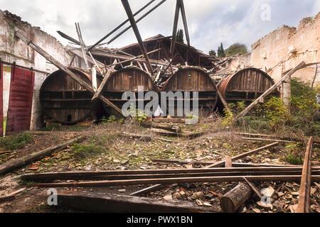 Abandonado grandes barriles de vino tumbado junto a una pared en un castillo abandonado en Francia. Imagen De Stock