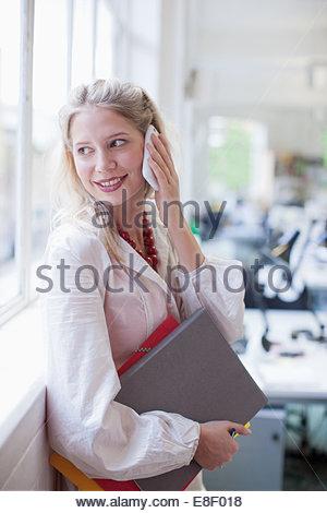 La empresaria sonriente Celebración carpetas y hablando por teléfono celular en la oficina Imagen De Stock