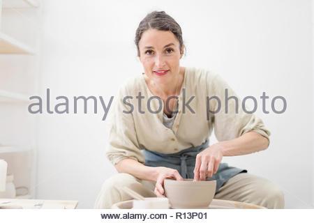 Retrato de una mujer sonriente haciendo cerámica en interiores Imagen De Stock