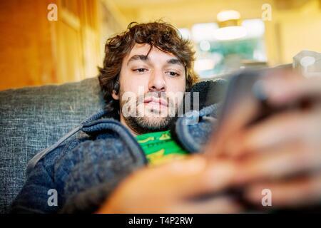 Joven permanece relajado con el smartphone en el sofá, Alemania Imagen De Stock