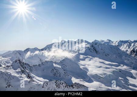 Las cumbres nevadas de los Alpes con retroiluminación. Imagen De Stock