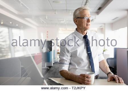 Pensativo empresario beber café en la oficina Imagen De Stock