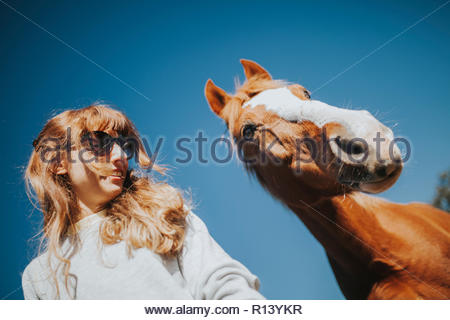 Retrato de una mujer y un caballo bajo un cielo azul Imagen De Stock