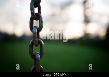 Cerca de varios eslabones de una cadena colgando contra un fondo fuera de foco en una profundidad de campo limitada. Imagen De Stock