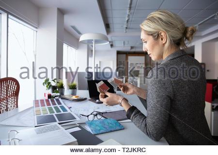 Diseñador de interiores femeninos examinar muestras en design studio Imagen De Stock