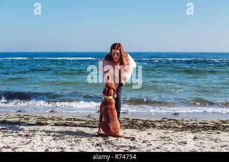 A mediados elegante mujer adulta, sobre la playa de acariciar a su perro, Odessa, Odeska Oblast, Ucrania Imagen De Stock