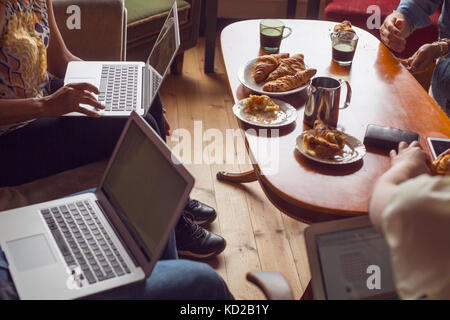 Personas sentadas en una mesa de café con ordenadores portátiles o teléfonos inteligentes. Imagen De Stock
