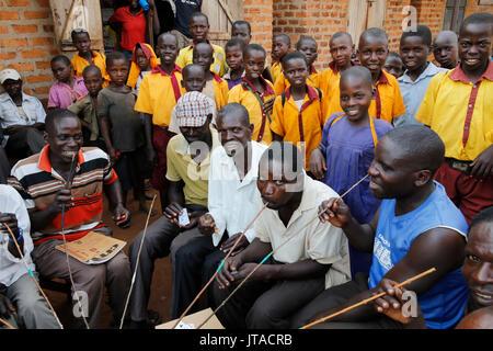 Los aldeanos ugandés bebiendo cerveza casera; y escolares, Bweyale, Uganda, África Imagen De Stock
