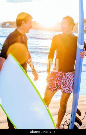 Surfistas masculinos con tablas de surf hablando sobre la soleada playa. Imagen De Stock