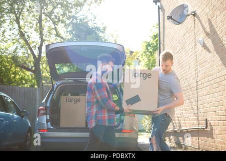Una pareja gay masculina descarga cajas de mudanza del automóvil Imagen De Stock