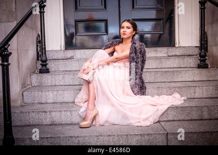 Retrato de mujer joven en vestido de noche sentado en pasos Imagen De Stock
