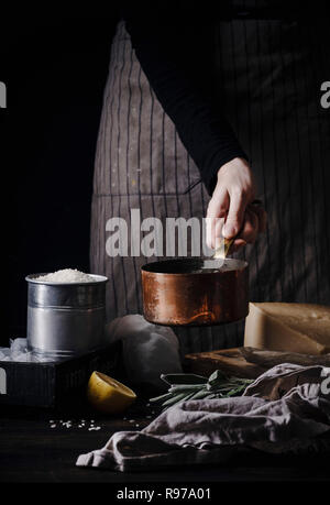Manos femeninas, risotto de cocción. El cobre pan, arroz, queso parmesano ingredientes. Fondo oscuro Imagen De Stock