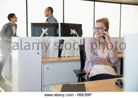La empresaria sonriente hablando por teléfono celular en la oficina Imagen De Stock