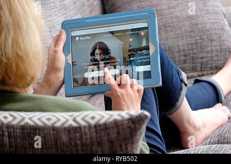 Persona sosteniendo el equipo tablet sentando en el sofá mirando website Imagen De Stock