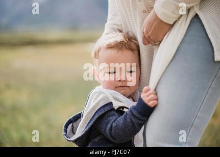 Hijo afectuoso aferrándose a las piernas de la madre Imagen De Stock