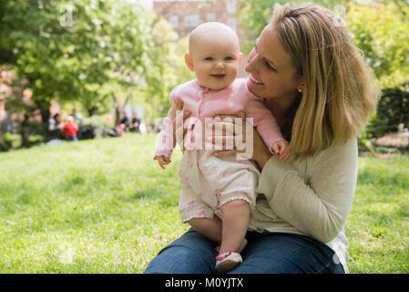 Retrato de madre sosteniendo caucásica hija en estacionamiento Imagen De Stock