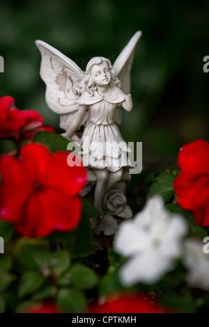 Una pequeña piedra, ángel o hada con alas de figurillas entre flores rojas y blancas. Imagen De Stock