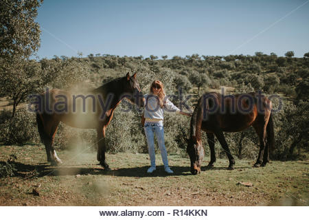 Una mujer en permanente entre dos caballos en un campo Imagen De Stock