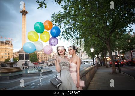 Dos amigas jóvenes en trajes de noche posando con globos, Trafalgar Square, Londres, Reino Unido. Imagen De Stock