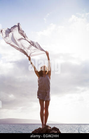 Mujer de pie sobre una roca cerca del océano, la celebración de tejido en el viento. Imagen De Stock