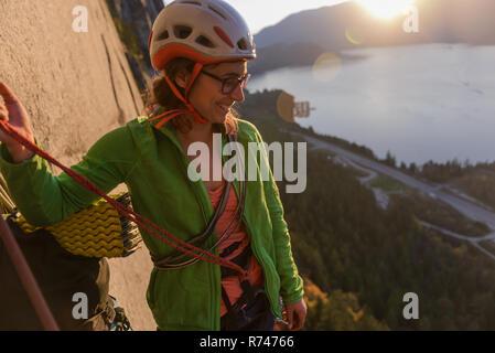 Las hembras jóvenes de escalador mirando hacia abajo desde el Jefe al atardecer, Squamish, British Columbia, Canadá Imagen De Stock