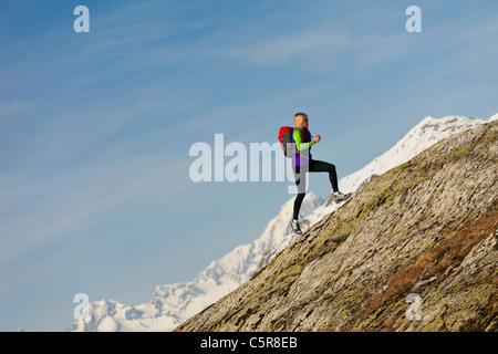 Un corredor ejecuta una roca empinada de la montaña a gran altitud. Imagen De Stock