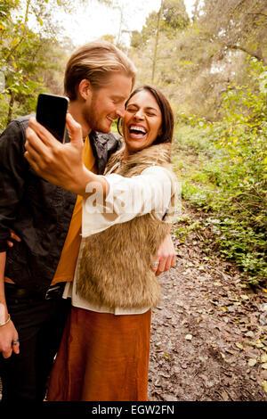 Mujer y hombre teniendo un selfie en el bosque. Imagen De Stock