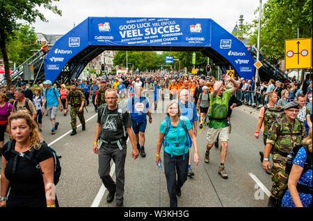 Los participantes cruzar la línea de meta durante el primer día.Ya que es el más grande del mundo multi-día caminando, el evento de cuatro días de marzo es visto como el primer ejemplo de deportividad y pegado internacional entre militares y civiles y de las mujeres de muchos países diferentes. Los participantes en la 103ª comenzaron los cuatro días marchas en Nijmegen, en la Wadren a las 4am, cruzaron el puente Waalbrug (la legendaria de Nijmegen), y pasando por la ciudad de Elst (el día), donde el color oficial era azul. El día era frío, con temperaturas inferiores a las de otros años. Imagen De Stock