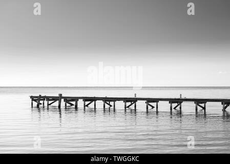 Muelle de madera sobre el mar en calma el agua como minimalismo en fondo blanco y negro impresionante Imagen De Stock