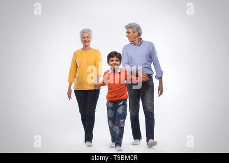 Los abuelos y nieto, tomados de la mano y caminar juntos Imagen De Stock