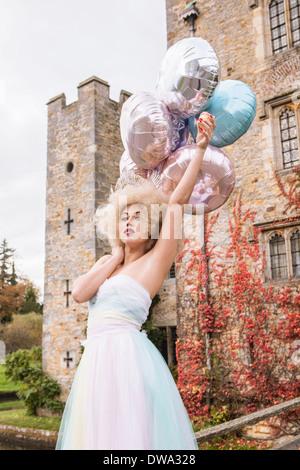 Novia fuera del castillo, la celebración de los globos Imagen De Stock