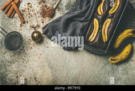 Flat-lay de chocolate recién horneadas postre torta de pan de banana en un molde para horno de rack de refrigeración con canela y cacao en polvo sobre la ficha de hormigón gris Imagen De Stock