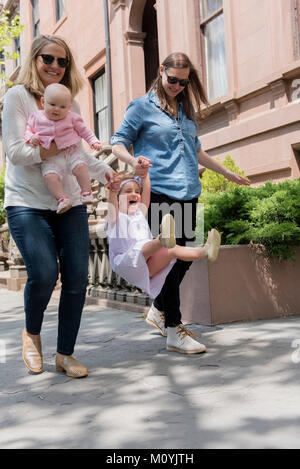 Las madres caucásica hija oscilante sobre las aceras de la ciudad Imagen De Stock
