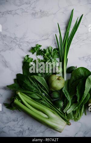 La comida verde fresca, variedad de hortalizas, verduras y frutas en superficie de mármol. Concepto de alimentación saludable. Idea monocromática. Imagen De Stock