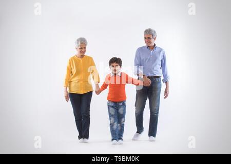 Los abuelos manteniendo a sus nietos y caminar de mano Imagen De Stock