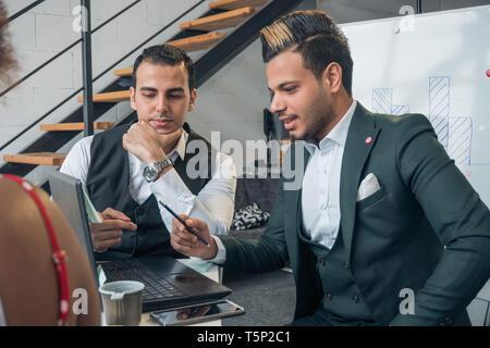Los jóvenes nacionales diferentes preparar una presentación comercial y mirar en el ordenador portátil. El concepto de la reunión en la oficina Imagen De Stock