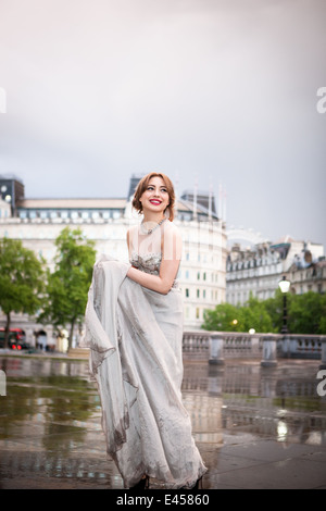 Mujer joven sosteniendo el vestido de noche húmeda, Trafalgar Square, Londres, Reino Unido. Imagen De Stock