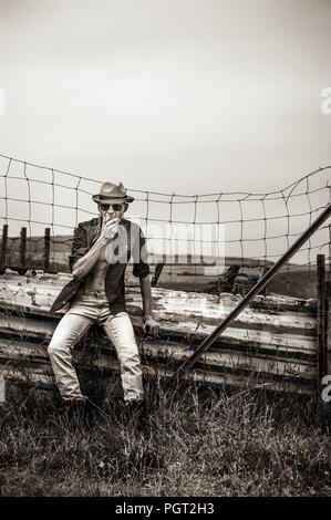 Joven hombre vestido con sombrero de paja de pie en los campos Imagen De Stock