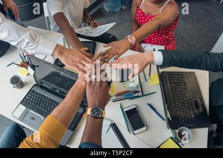 Jóvenes de diferentes nacionalidades, celebrar una reunión en un moderno y elegante oficina. Socios pliega las manos en señal de amistad. Imagen De Stock
