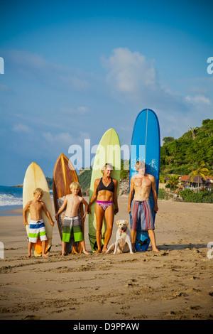 Familia de pie en la playa con tablas de surf Imagen De Stock