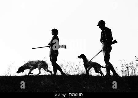 1920 1930 silueta anónima al hombre y a la mujer los cazadores que portan armas, cada uno con un perro de caza - s2541 HAR001 HARS SILUETAS DE OCIO Y RECREO CANINOS POOCH Conexión anónima COOPERACIÓN CANINA ARMA ARMAS DE FUEGO CAZADORES mamífero adulto medio hombre adulto medio Mediados de-MUJER ADULTA COMPAÑERISMO EN BLANCO Y NEGRO HAR001 ANTICUADO Imagen De Stock