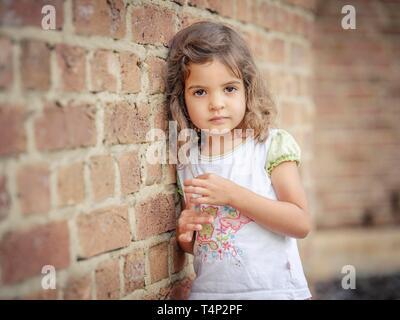 Niña de 3 años de edad, apoyado contra una pared, retrato, Alemania Imagen De Stock