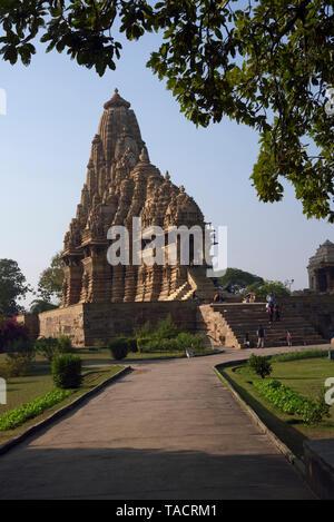 SSK - 1134 bellamente y exquisitamente ordenados nombrado como el Templo Kandariya Mahadev dedicado al dios hindú Shiva El Señor con un camino cementado en primer plano y enmarcado por las ramas del árbol Khajuraho, Madhya Pradesh, India Asia el 18 de diciembre de 2014 Imagen De Stock