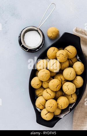 Mini tahini galletas en un recipiente oval negro fotografiado sobre un fondo gris. Azúcar en polvo en un pequeño tamiz en el lateral. Imagen De Stock