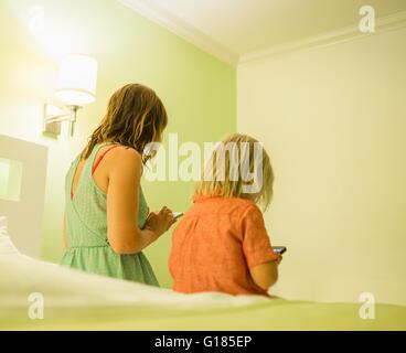 Madre e hijo mediante el smartphone en la cama Imagen De Stock